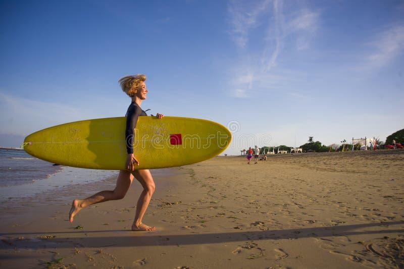 Menina loura atrativa e feliz nova do surfista na praia bonita que leva a placa de ressaca amarela que corre fora do mar que apre fotos de stock royalty free