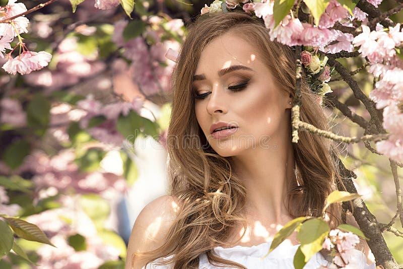 Menina loura atrativa no jardim de florescência fotografia de stock