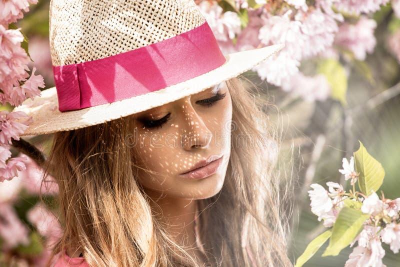 Menina loura atrativa no jardim de florescência imagem de stock