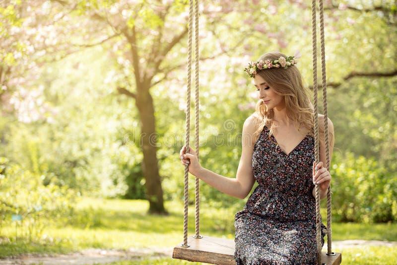 Menina loura atrativa no jardim de florescência fotografia de stock royalty free