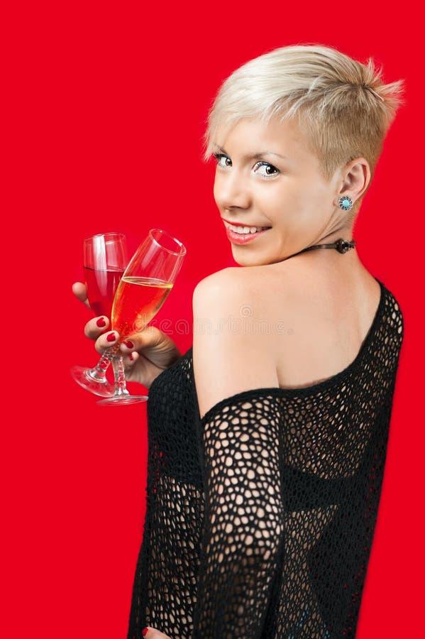Menina loura atrativa que guarda o vidro do vinho tinto imagem de stock royalty free