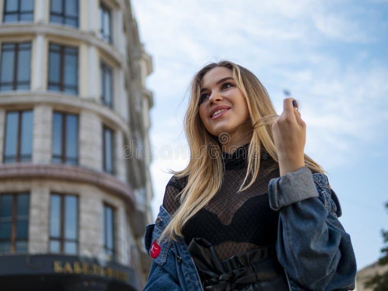 Menina loura atrativa que sorri em um revestimento da sarja de Nimes no fundo de uma construção moderna e de um céu azul imagens de stock royalty free