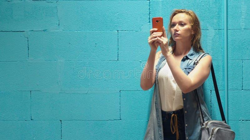 A menina loura atrativa usa o smartphone vermelho contra uma parede azul fotos de stock royalty free