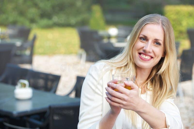 A menina loura bebe o chá no café fotografia de stock royalty free