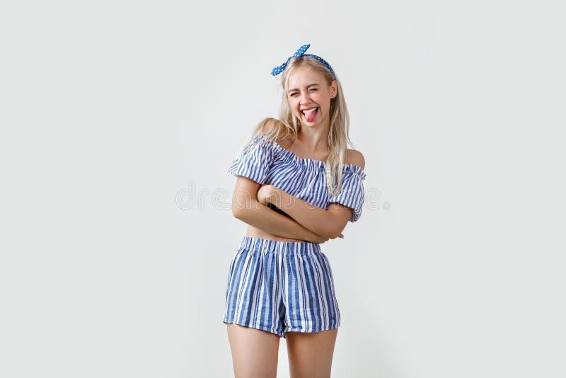 Menina loura bonita alegre e entusiasmado no equipamento do verão, língua da exibição, levantando na câmera, estando sobre o bran foto de stock