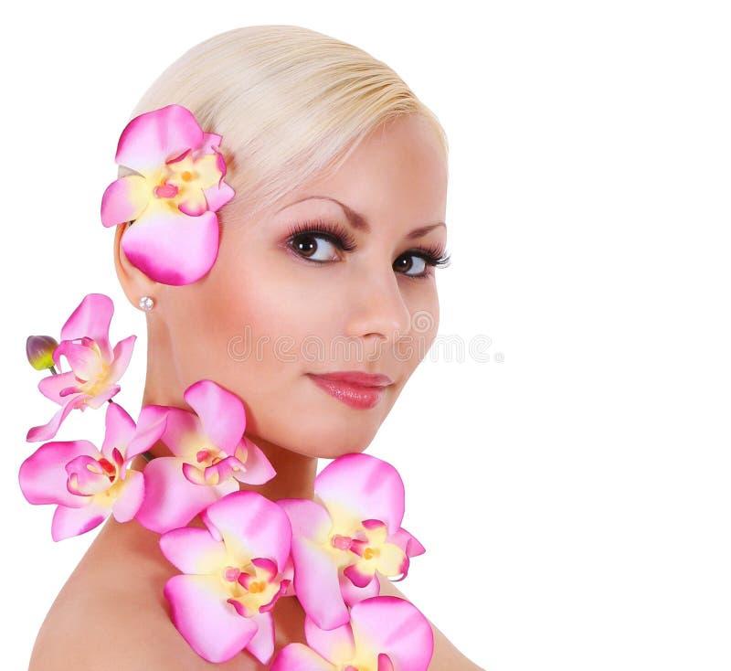 Menina loura bonita com as flores cor-de-rosa da orquídea isoladas fotos de stock
