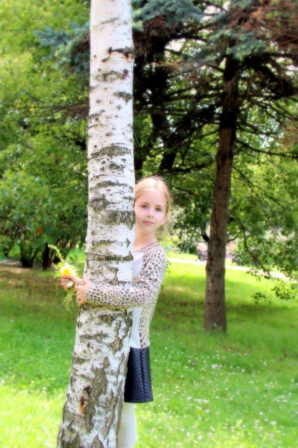 Menina loura bonita com as flores que abraçam a árvore de vidoeiro imagem de stock royalty free