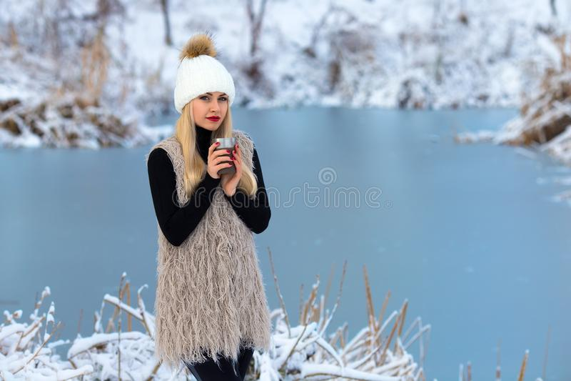 Menina loura bonita com bebida quente no inverno fotos de stock