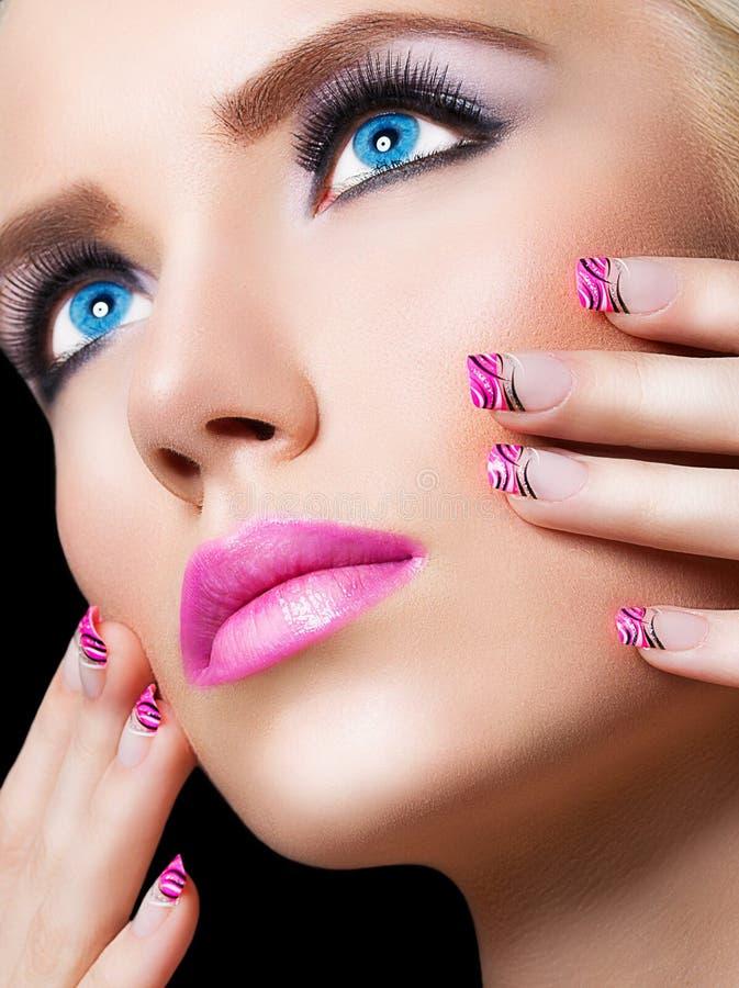 Menina loura bonita com bordos e os pregos cor-de-rosa fotografia de stock royalty free