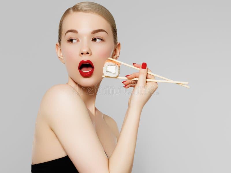 Menina loura bonita com bordos vermelhos e os pregos manicured que come o sushi, alimento japonês saudável Terra arrendada bonita foto de stock royalty free