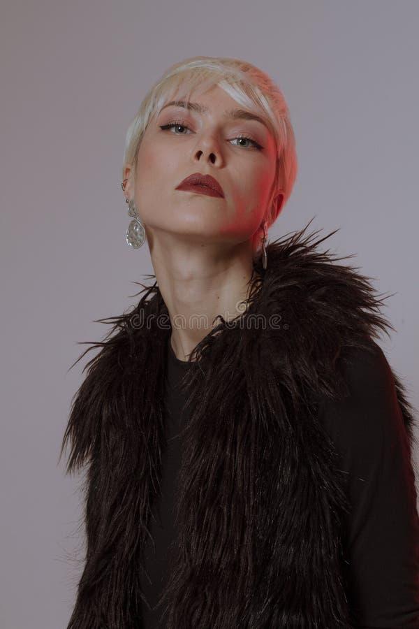 Menina loura bonita com cabelo curto e composição em um casaco de pele preto fotos de stock