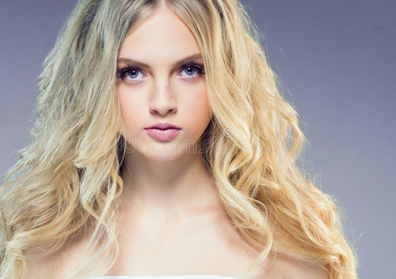 Menina loura bonita com cabelo encaracolado longo sobre o backgroun roxo foto de stock royalty free