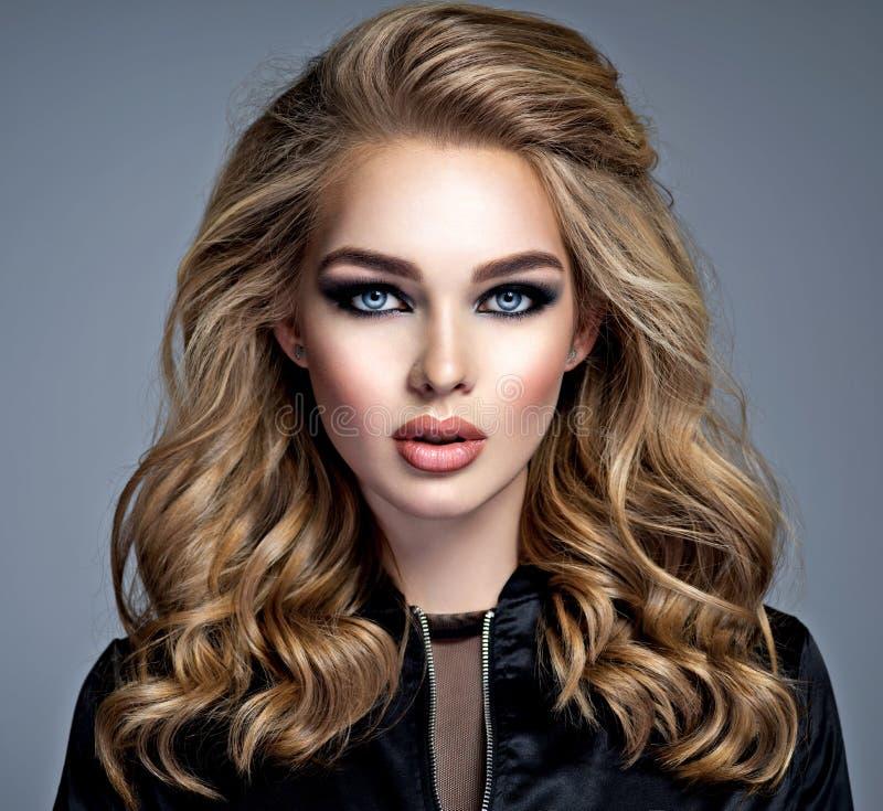 Menina loura bonita com composição nos olhos fumarentos do estilo fotos de stock