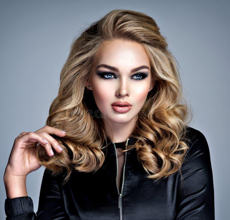Menina loura bonita com composição nos olhos fumarentos do estilo fotos de stock royalty free