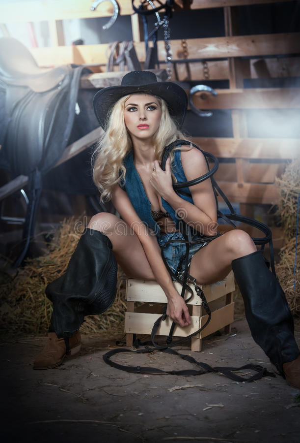 A menina loura bonita com olhar do país, disparou dentro no estilo estável, rústico Mulher atrativa com o chapéu e o short pretos fotografia de stock
