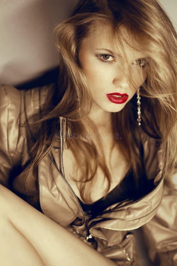 Menina loura bonita com os bordos vermelhos 'sexy' no casaco de cabedal imagens de stock