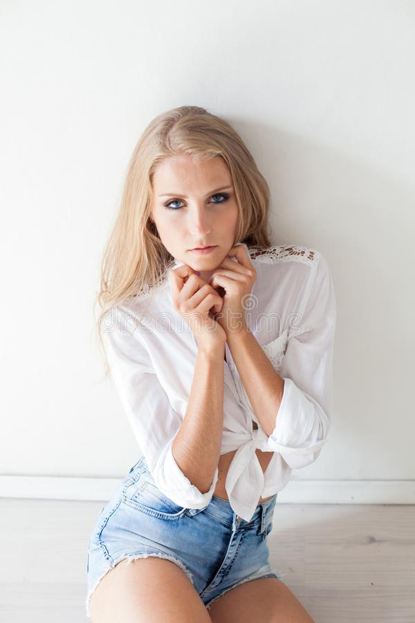 Menina loura bonita com os olhos azuis que sentam-se no assoalho em uma sala branca 1 imagem de stock
