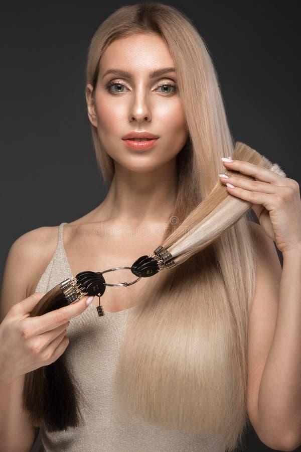 A menina loura bonita com um cabelo perfeitamente liso, cl?ssico comp?e com uma paleta para extens?es do cabelo nas m?os imagens de stock royalty free