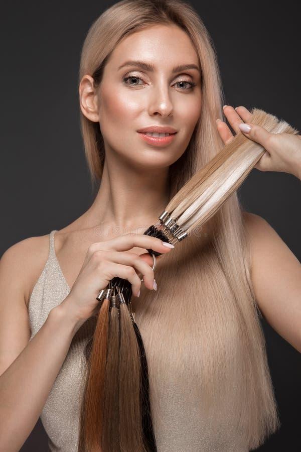 A menina loura bonita com um cabelo perfeitamente liso, cl?ssico comp?e com uma paleta para extens?es do cabelo nas m?os foto de stock royalty free