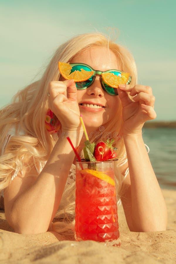 Menina loura bonita com um cocktail bonito vermelho em suas mãos pelo mar/rio imagem de stock