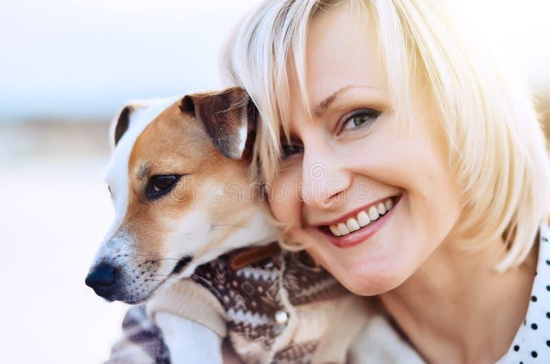 Menina loura bonita com um sorriso e um cão Face feliz imagens de stock royalty free