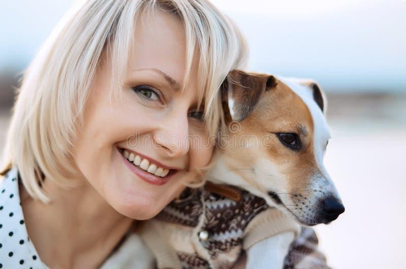 Menina loura bonita com um sorriso e um cão Face feliz fotografia de stock