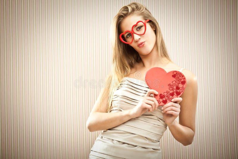 Menina loura bonita com vidros do coração com o presente do amor da caixa do chocolate imagem de stock