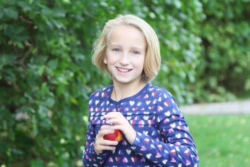 A menina loura bonita da criança em uma caminhada no parque come o fruto, a nectarina ou o pêssego imagens de stock royalty free