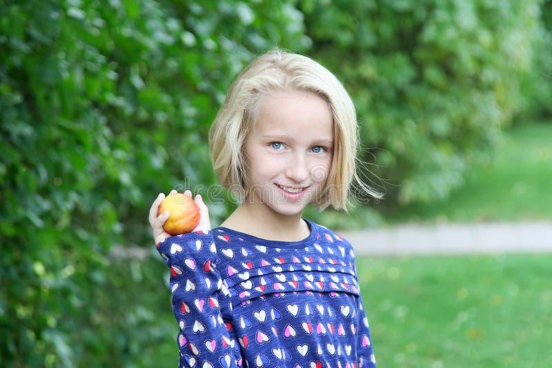 A menina loura bonita da criança em uma caminhada no parque come o fruto, a nectarina ou o pêssego imagem de stock royalty free