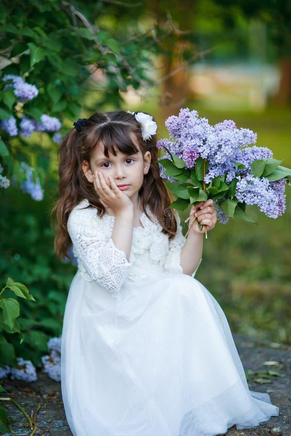 A menina loura bonita da criança está vestindo a grinalda de flores lilás fotos de stock royalty free