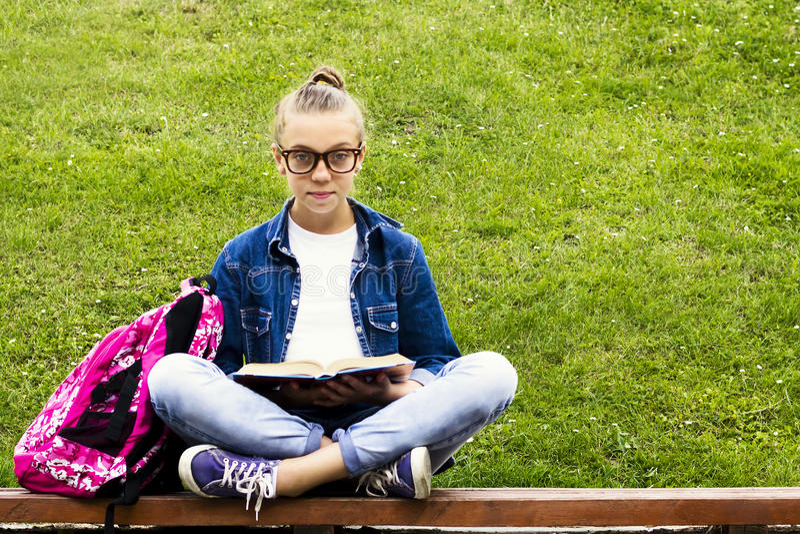 Menina loura bonita da estudante na camisa das calças de brim que lê um livro na grama com uma trouxa na educação do parque imagens de stock
