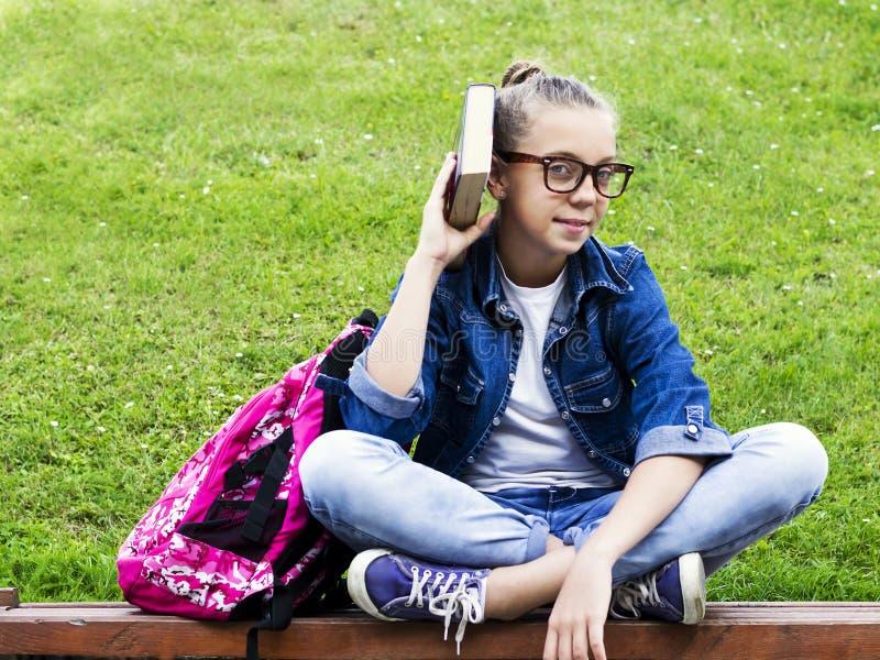Menina loura bonita da estudante na camisa das calças de brim que lê um livro na grama com uma trouxa na educação do parque imagens de stock royalty free