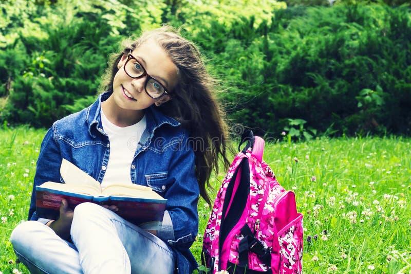 Menina loura bonita da estudante na camisa das calças de brim que lê um livro na grama com uma trouxa no parque fotografia de stock royalty free