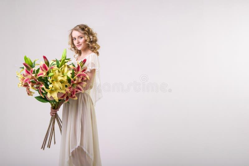 A menina loura bonita da mola com ramalhete grande floresce foto de stock