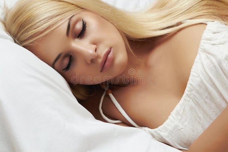 Menina loura bonita de sono. mulher da beleza. cama branca imagens de stock