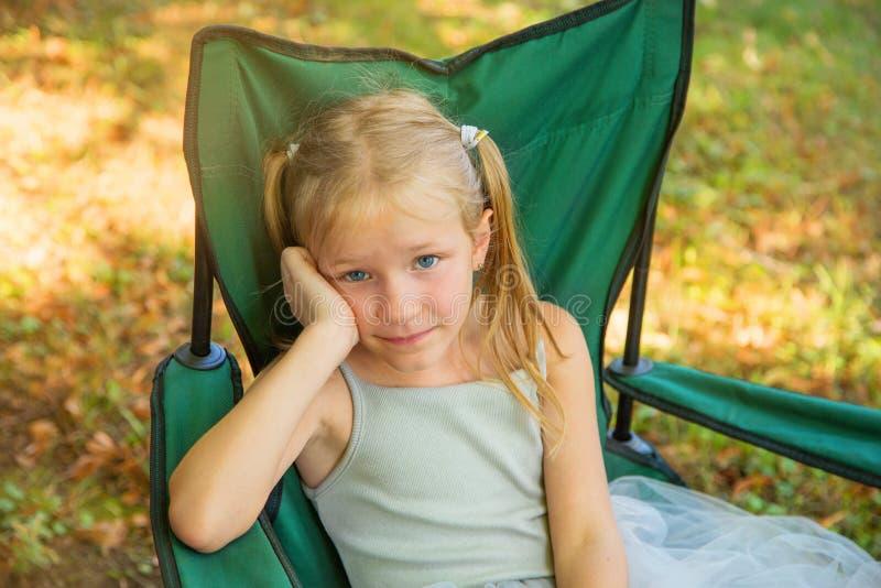 A menina loura bonita dos olhos azuis que senta-se em uma cadeira na menina cansado da jarda ou do parque tem um resto fotos de stock