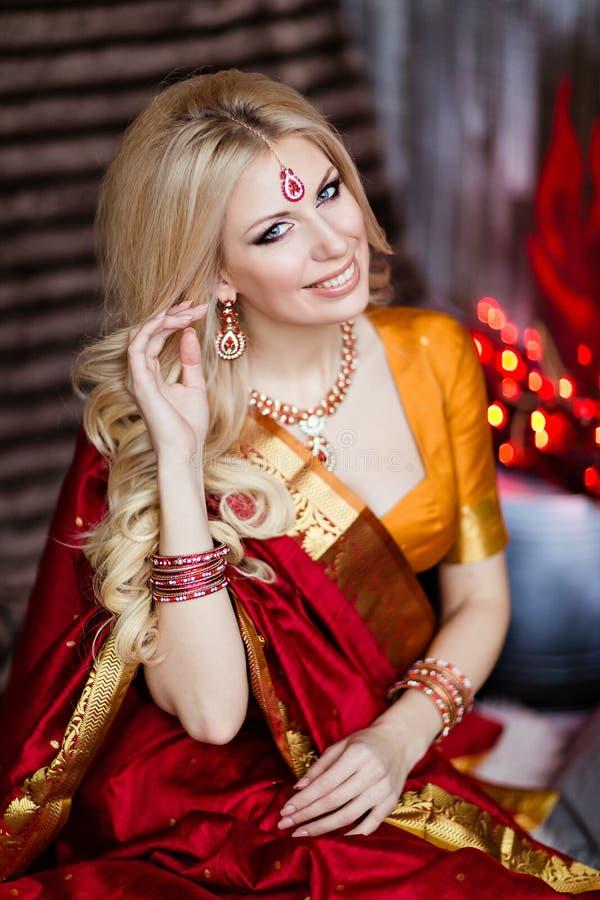 A menina loura bonita e sensual no saree do vermelho indiano senta-se na fotografia de stock