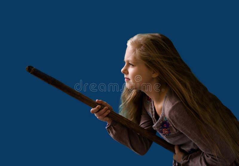 Menina loura bonita em um cabo de vassoura sob a forma do fundo do azul da bruxa fotografia de stock