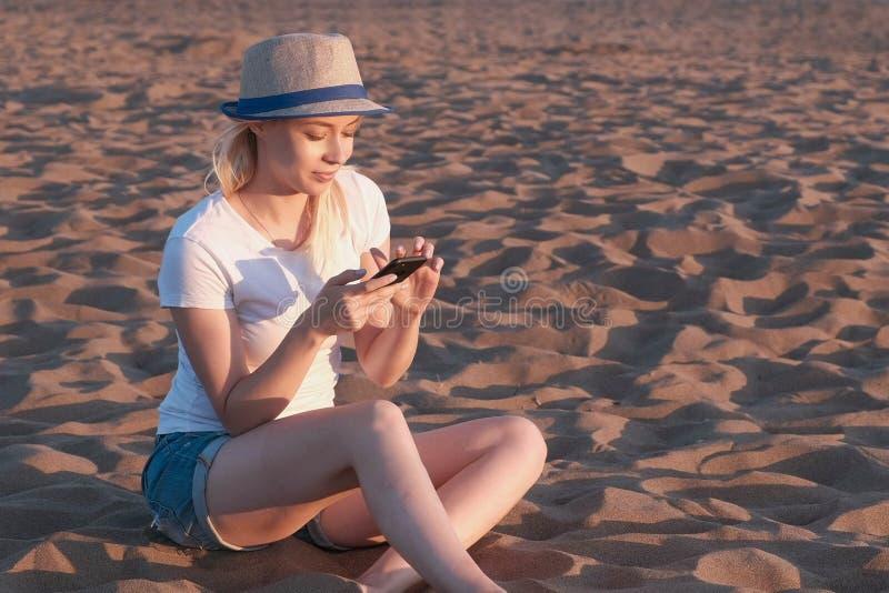 A menina loura bonita em um chapéu datilografa uma mensagem em seu telefone celular na praia no por do sol foto de stock royalty free
