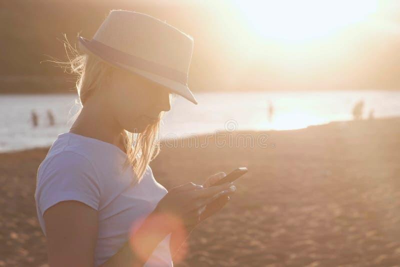 A menina loura bonita em um chapéu datilografa uma mensagem em seu telefone celular na praia no por do sol imagem de stock royalty free
