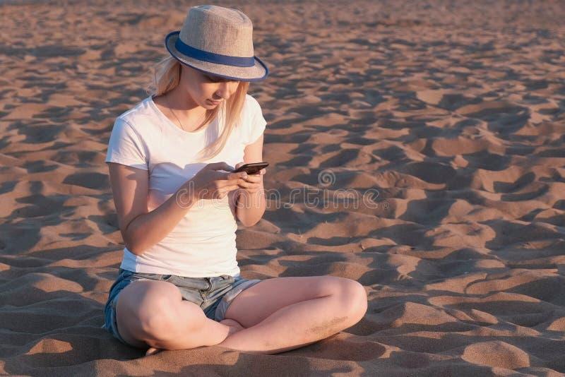 A menina loura bonita em um chapéu datilografa uma mensagem em seu telefone celular na praia no por do sol foto de stock