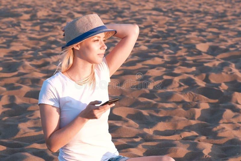 A menina loura bonita em um chapéu datilografa uma mensagem em seu telefone celular na praia no por do sol fotografia de stock royalty free
