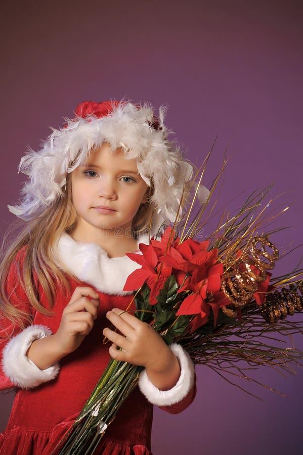 Menina loura bonita em um chapéu do Natal com um bouque do Natal fotografia de stock royalty free