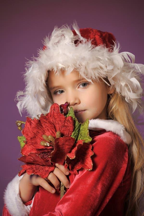 Menina loura bonita em um chapéu do Natal com um bouque do Natal fotografia de stock