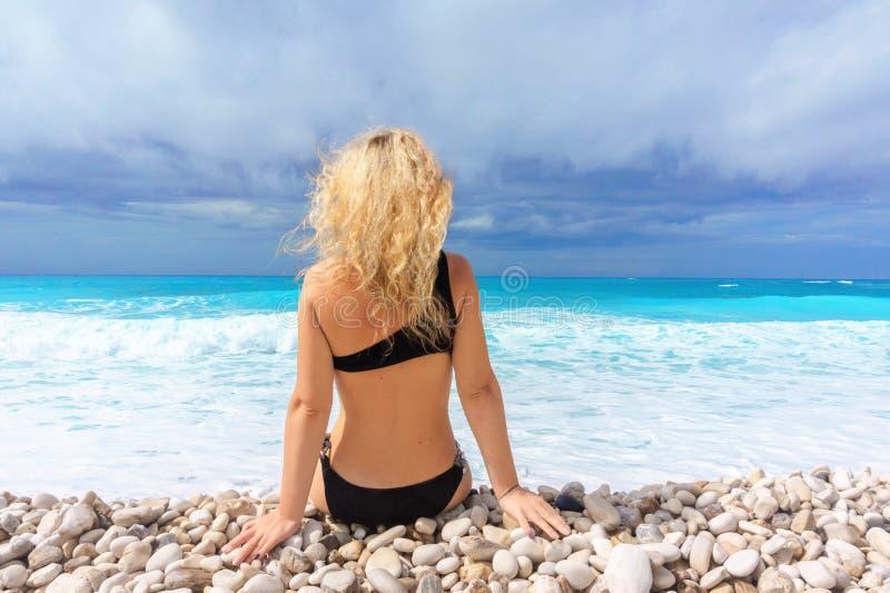 A menina loura bonita em um roupa de banho preto senta-se em uma praia das caraíbas vazia foto de stock