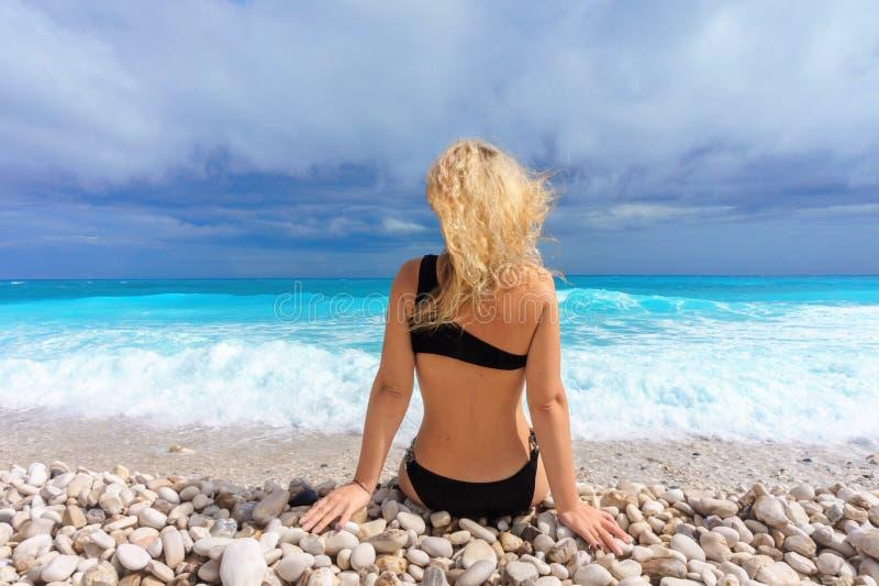 A menina loura bonita em um roupa de banho preto senta-se em uma praia das caraíbas vazia fotografia de stock royalty free