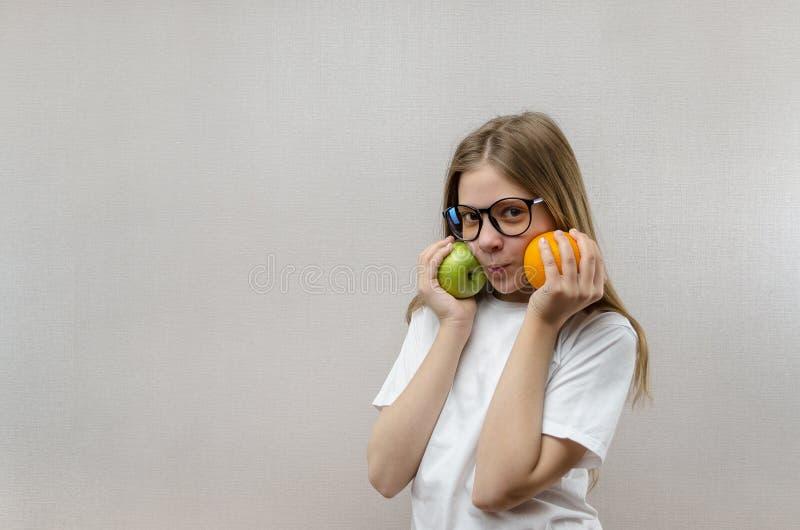A menina loura bonita em um t-shirt branco sorri e guarda uma ma?? e uma laranja em suas m?os Nutri??o saud?vel para fotos de stock