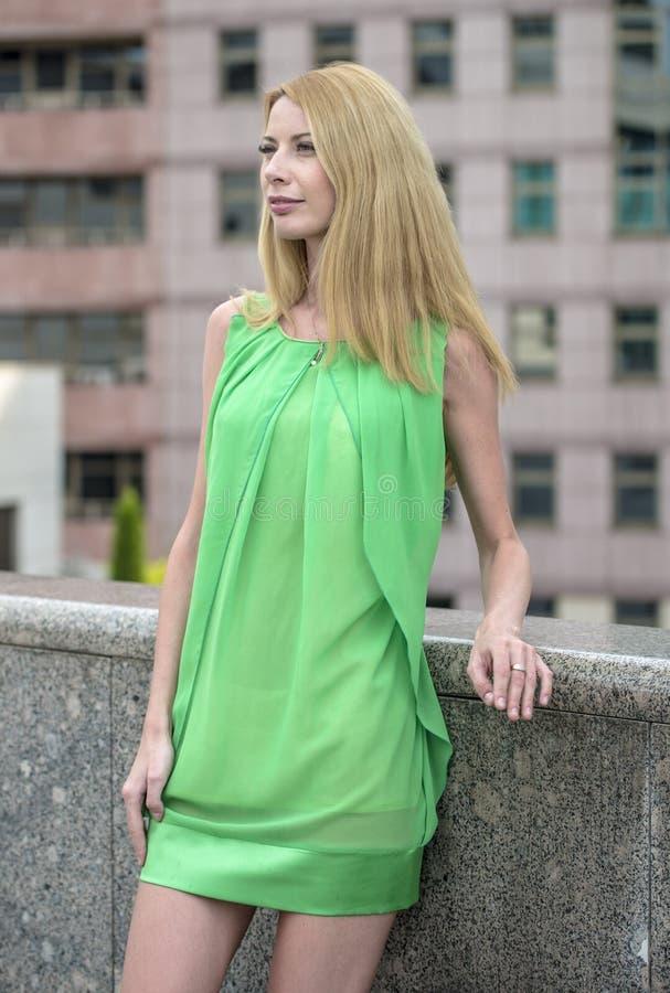 Menina loura bonita em um vestido curto verde do verão nas ruas da cidade imagens de stock royalty free
