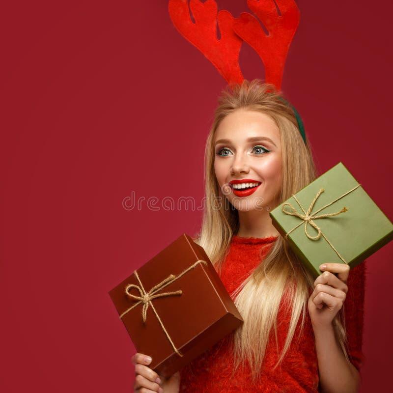 Menina loura bonita em uma imagem de ano novo com as caixas dos presentes nas mãos e nos chifres dos cervos em sua cabeça A belez imagem de stock royalty free
