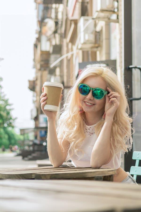 A menina loura bonita na cidade está bebendo o café Sessão de foto da rua Copo cinzento com uma tampa branca e um lugar para o lo fotos de stock